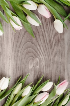 Frame from bright tulips on wood