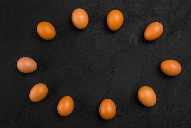Frame from brown chicken eggs on black table