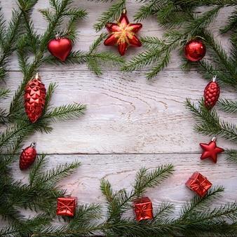 Рамка из веток елки и красных украшений на светлом деревянном фоне