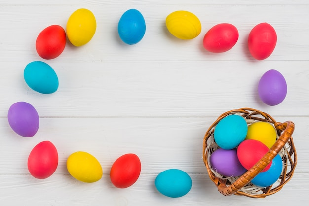 Frame from colorful easter eggs and basket on table