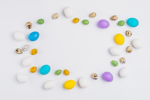 Frame from colorful easter eggs on white table