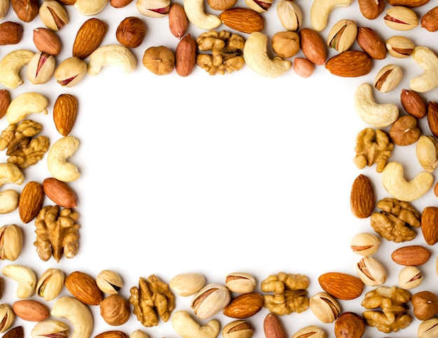 Frame from different nuts on white background, top view.