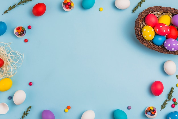 Frame from easter eggs and basket on table