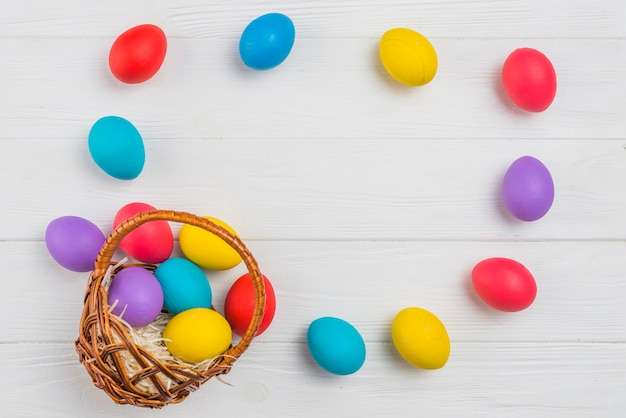 Frame from easter eggs and basket on wooden table