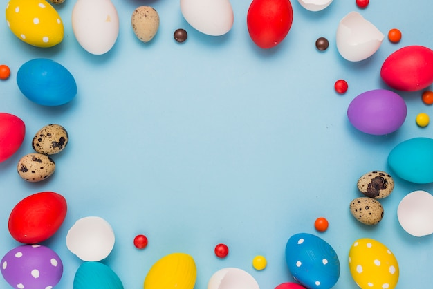 Frame from easter eggs and candies on blue table