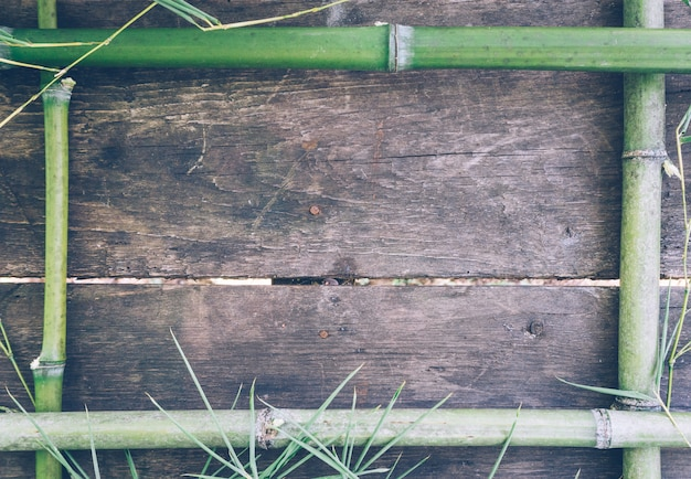 Frame from green bamboo on an old rustic wooden table.
