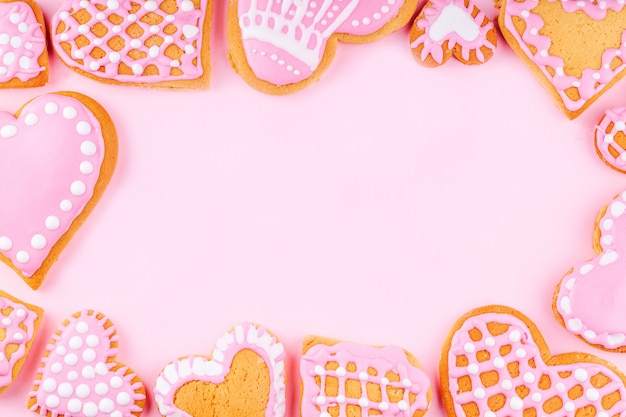 Frame from handmade glazed decorated heart shaped cookies on pink background