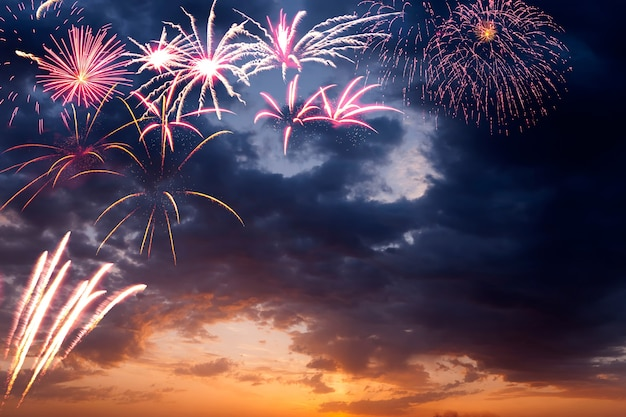 Кадр из праздничного фейерверка в вечернем небе с величественными облаками, длительная выдержка