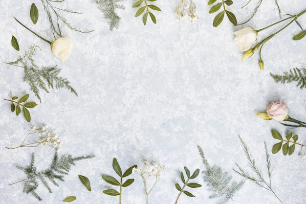 Frame from rose flowers and plant branches on table