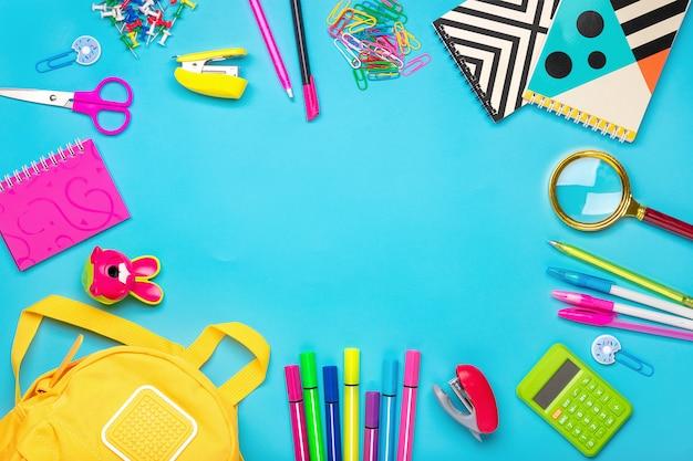 Кадр из школьных и канцелярских принадлежностей на синем фоне плоская планировка вид сверху обратно в школу, концепция образования