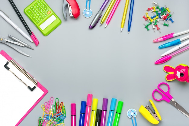 Кадр из школьных и офисных принадлежностей скрепки, ножницы, ручки, фломастеры, точилка, калькулятор, степлер, изолированные на сером фоне плоская планировка вид сверху вернуться к концепции школы