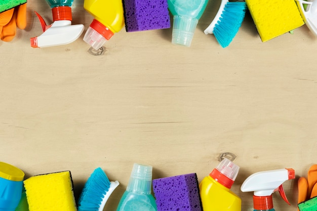 Рама из различных чистящих средств, спреев, бутылок, щетки, губки, резиновых перчаток на деревянном полу с копией пространства, вид сверху. концепция уборки дома