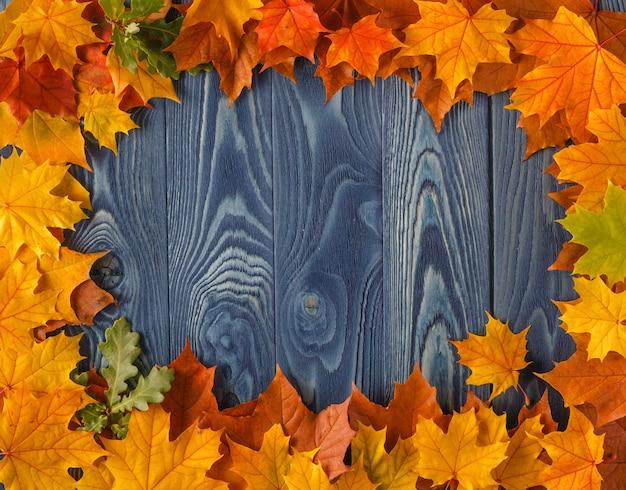 Кадр из ярких красочных осенних листьев на гранж деревянный голубой стол, старинный сезонный фон