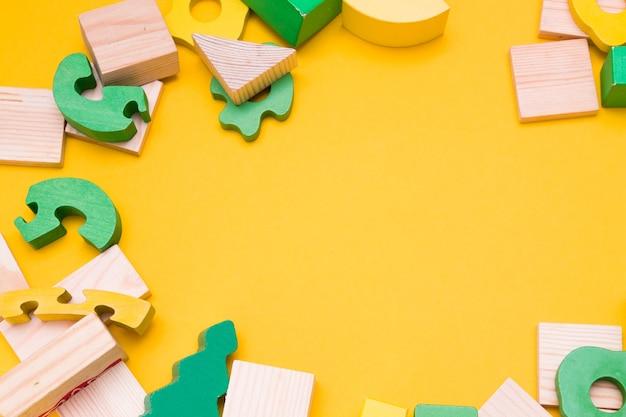 黄色の背景に木のおもちゃのフレーム。コピースペース;上面図;黄色と緑の色の木からのパズルとデザイナー、ペイントなし