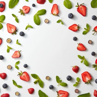 Frame of fruit pattern with strawberries, blueberries and mint leaves on a white background, flat