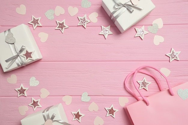 Frame gift box with ribbon and confetti on pink table