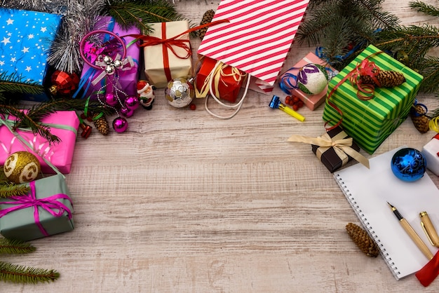 Frame of gift boxes and fir branches on wooden table. christmas celebration
