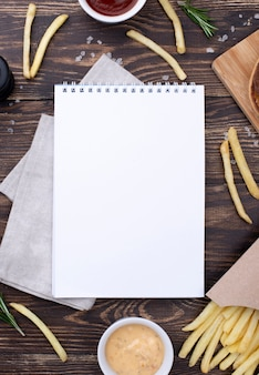 Frame of hamburger and fries beside notebook