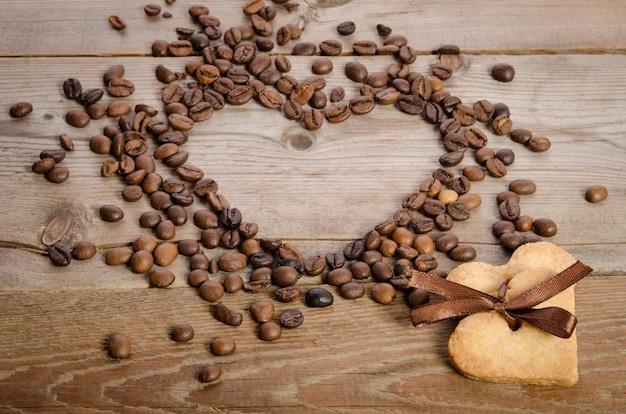 Рамка-сердце из кофейных зерен и печенья-сердце, связанных вместе на деревянном столе