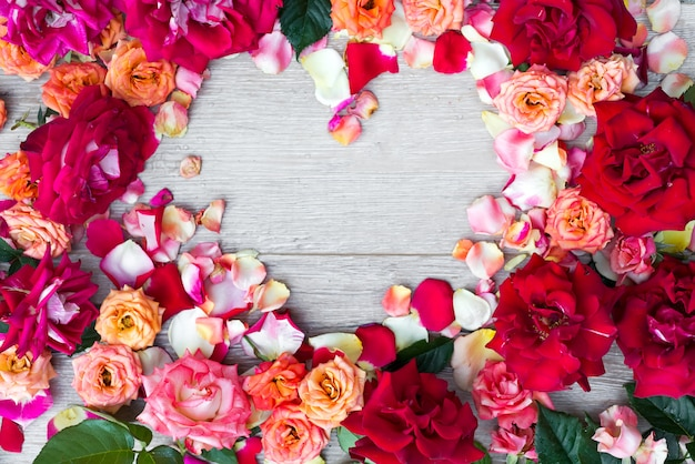Frame heart made of rose flowers on wooden background for valentines day.