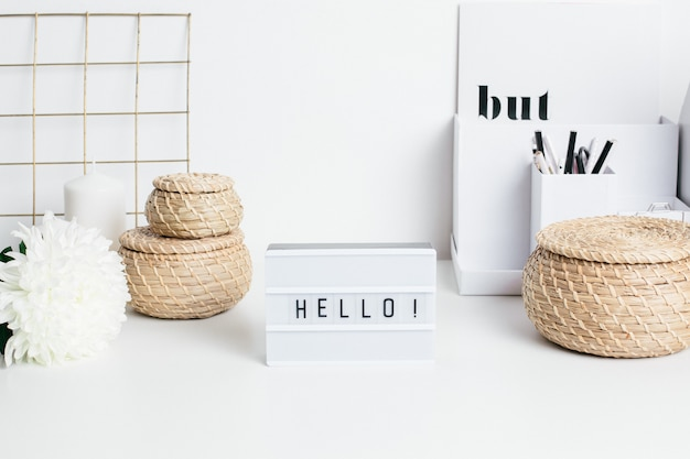 Frame hello on white table with a flower and straw baskets