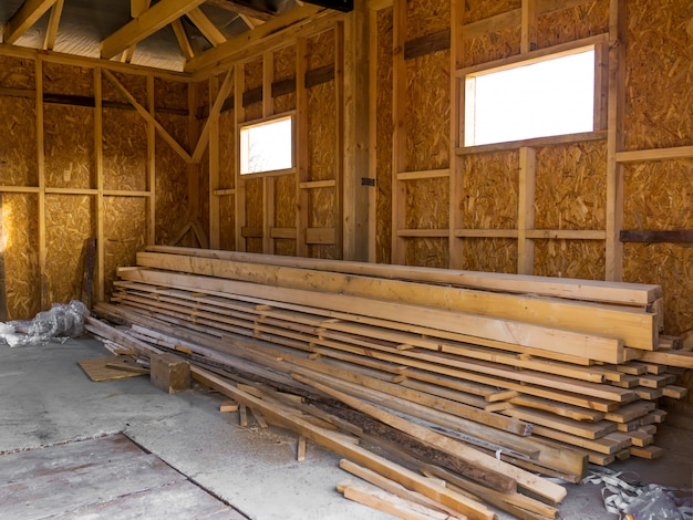 Frame house made of timber. lumber in the pile