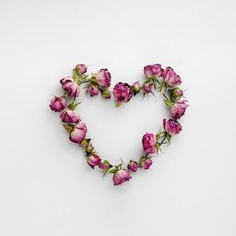乾燥したピンクのバラで作られたハート形のフレーム。バレンタインデーと愛の概念