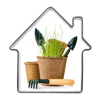 白い背景で隔離の苗のシャベルと熊手で泥炭ポットをガーデニングするための経済的なストックとツールを備えた形の家のフレーム