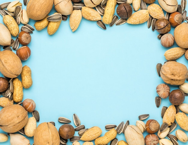 The frame is made of a mixture of nuts on a blue . vegetarian food.