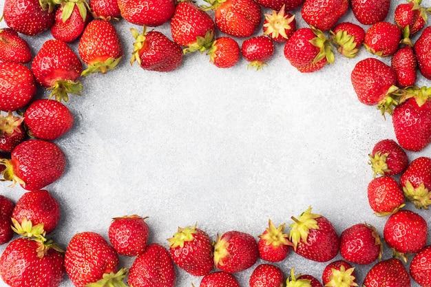 コンクリートの背景にジューシーな熟したイチゴをフレームします。甘くてヘルシーなデザート、ビタミンの収穫。コピースペース。