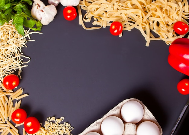 Frame of macaroni and vegetables on the black background.
