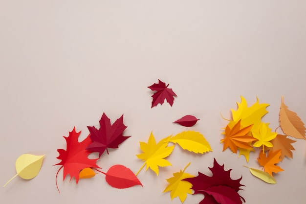 A frame made of autumn leaves on a beige background. the leaves are cut out of paper. autumn concept
