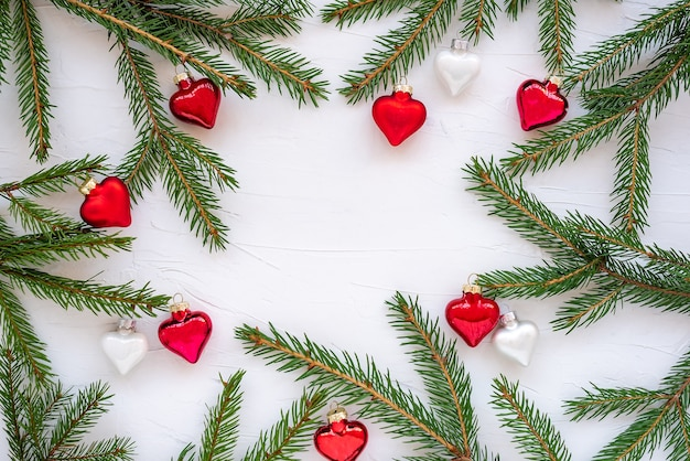 Frame made of branches of christmas tree and glass decorations in shape of hearts.
