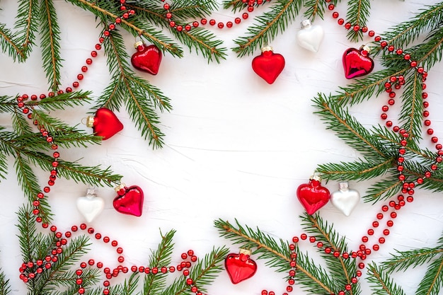 Frame made of branches of christmas tree and glass decorations in the shape of hearts.