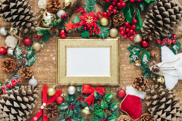 Frame made of christmas decor and fir branches on wooden background.