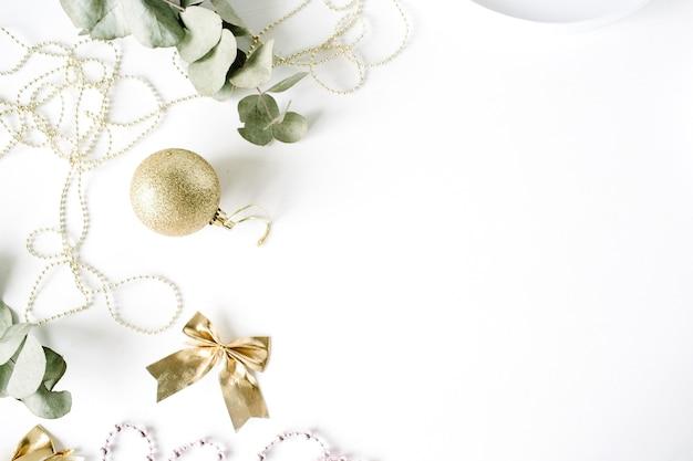 Frame made of christmas decoration with christmas glass balls, tinsel, bow, eucalyptus.