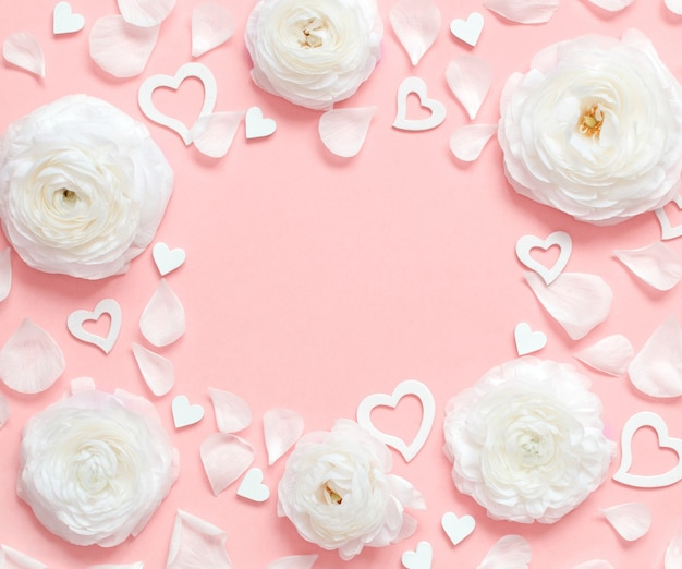 Frame made of cream flowers, petals and hearts on a light pink top view