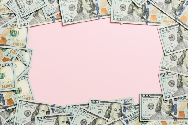 Frame made of dollars with copy space in the middle. top view of business concept on pink background with copy space.