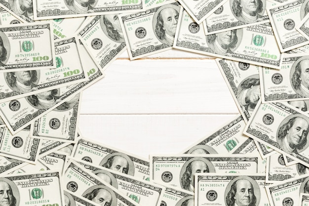 Frame made of dollars with copy space in the middle. top view of business concept on white wooden background with copy space