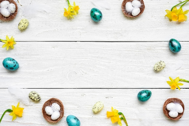 Frame made of easter eggs, spring flowers and feathers on white wooden table. easter composition