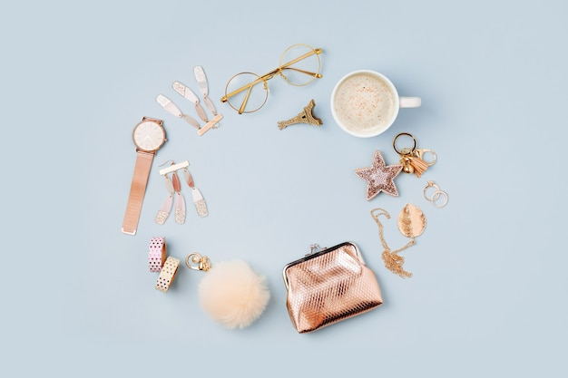 Frame made of female accessory and coffee cup on blue background. flat lay