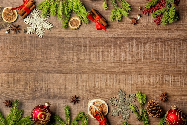 Frame made of fir tree branches and christmas decor on wooden background
