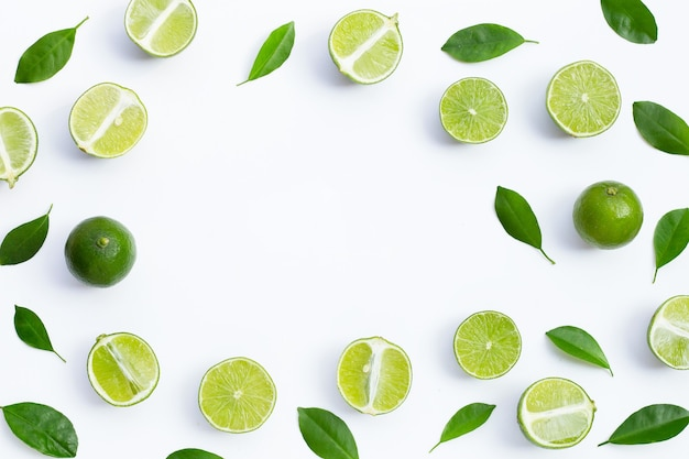 Frame made of fresh limes with green leaves on white background. top view