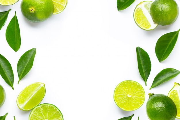 Frame made of fresh limes with green leaves on white background.