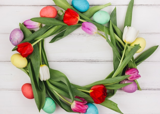 Frame made from easter eggs and tulips on table
