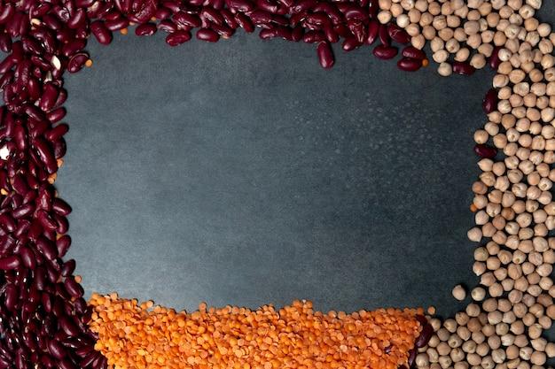 복사 공간 검정 배경 위에 콩의 그룹에서 만든 프레임. 콩, 렌즈 콩 및 검은 색 바탕에 병아리 완두콩의 그룹입니다.