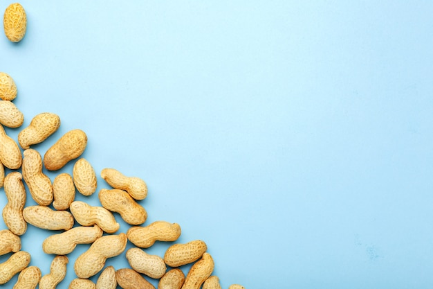Frame made of nuts peanuts in shell with copy space on blue colored background. flat lay with place for text for peanut butter, peanut paste. vegan food concept.