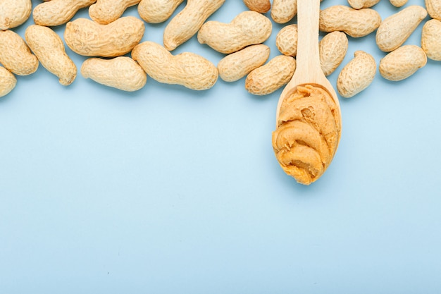 Frame made of nuts peanuts in shell and wooden spoon with creamy peanut butter copy space on blue