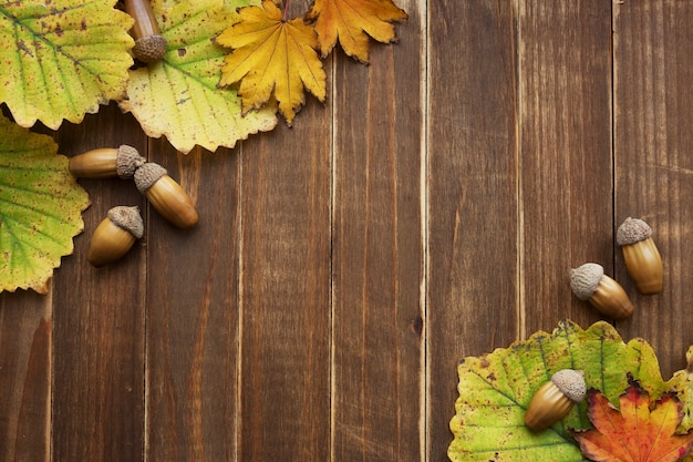 Рама из осенней желтой листвы и желудей на деревянном фоне с копией пространства.