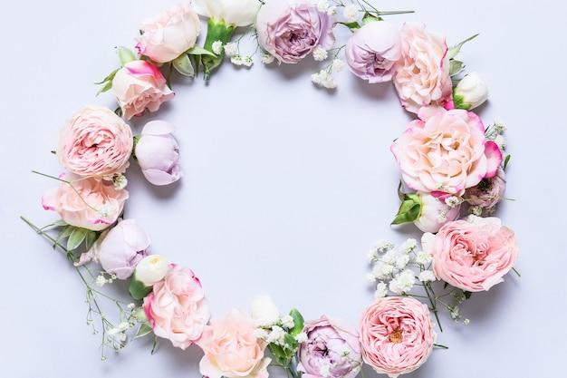 明るい表面に美しい花で作られたフレーム